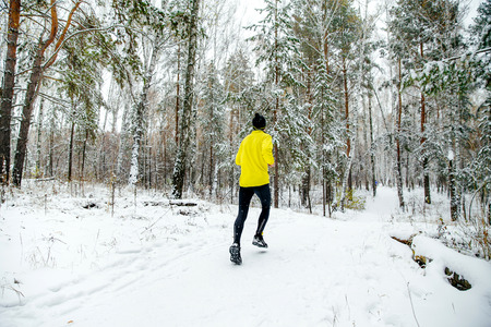 winter park: young man runner running a winter marathon on a snowy park Editorial