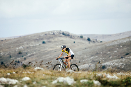 young man rider mountainbiker rides in mountains during Crimean race mountainbike Editorial