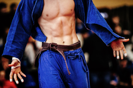 sixpack: muscular body in sixpack of athlete judoka in blue kimono with brown belt Stock Photo
