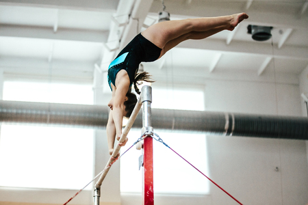 girl athlete gymnast exercises on uneven bars 스톡 콘텐츠