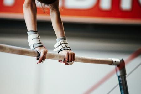 Hände junge Mädchen Turner Übung auf Stufenbarren Standard-Bild - 71804968