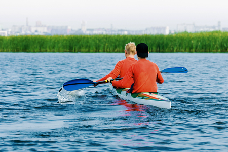 two young male athletes rowing in kayak