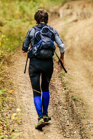 back woman with backpack and walking sticks runs trail Stock Photo