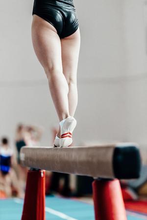 magnesia: back part of body female gymnast exercises on balance beam
