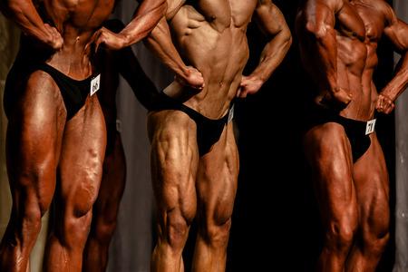 gare di bodybuilding tre atleti bodybuilder in posa più muscolare Archivio Fotografico