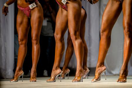 posing group slender legs women in heels competition fitness bikini