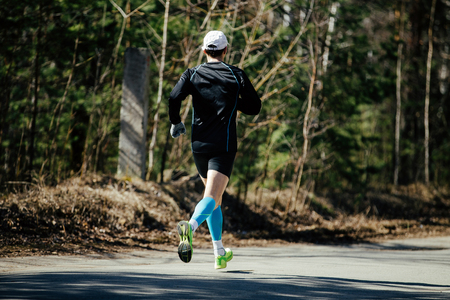 running man in compression socks competition in spring marathon in Park