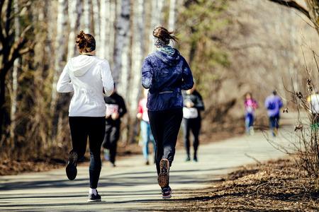 Morgenlaufgruppe Frauen laufen im sonnigen Stadtpark Standard-Bild - 76973646
