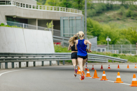 back two young women running in road with traffic cones safety Stock Photo
