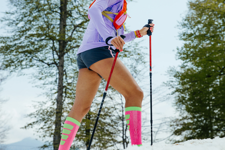 female running mountain snowy trail with trekking poles and compression socks