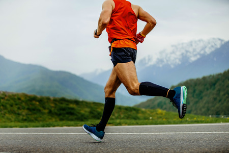 running man athlete compression socks on background mountains and green forest Stock Photo