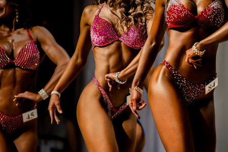 three young girls in swimsuits competition fitness bikini Banque d'images