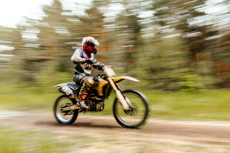 off road biking: blurred motion athlete bike enduro championship motocross in forest Stock Photo