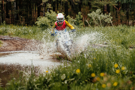 motorcycle enduro crosses puddles of water and mud in forest