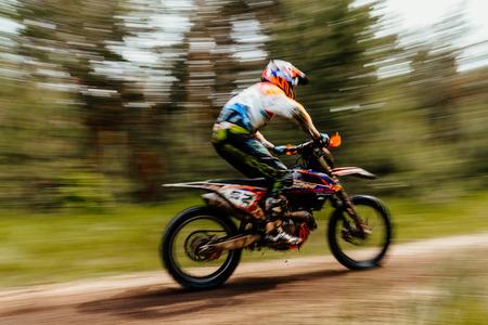 motorcross: blurred motion athlete bike enduro in forest trial racing motocross