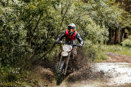 off road biking: enduro athlete on motorcycle crosses a puddle of water and mud racing motocross