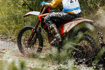 motocross enduro athlete on motorcycle crosses a puddle of water and mud