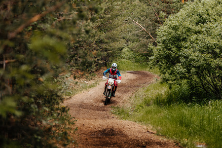 enduro athlete on bike rides in forest trial racing motocross