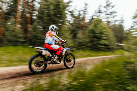 blurred motion motorcycle rider racing motocross in woods