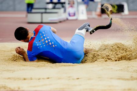 Zawodnik w skoku w dal niepełnosprawny ląduje w piasku
