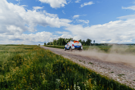 Filimonovo, Russia - July 10, 2017: rally car driving on a dust road in green grass and blue sky during Silk way rally