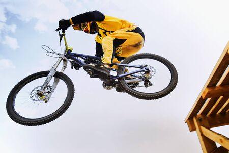 mtb: cyclist jump downhill mountain biking in sunlight Stock Photo