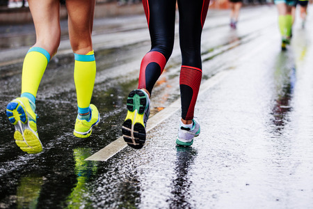 feet two girls athletes running on wet street urban marathon Imagens