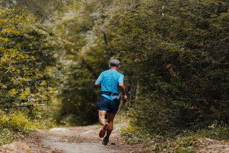 elderly man runner running in forest marathon