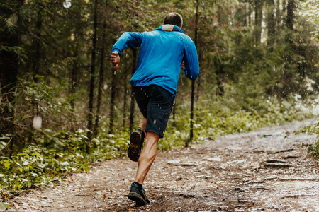 muscular male runner fast running forest trail in rain