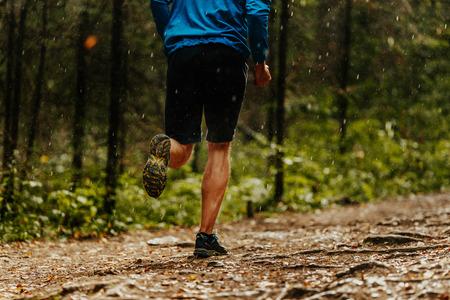 male runner athlete running forest trail in rain