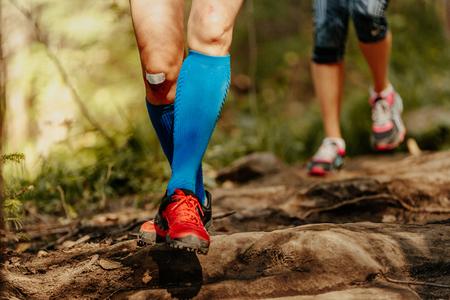 woman feet runner running rocks in blue compression socks