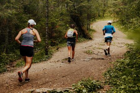 three runners running forest trail marathon race