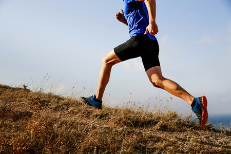 legs male athlete runner running uphill on trail background of sky Stock Photo