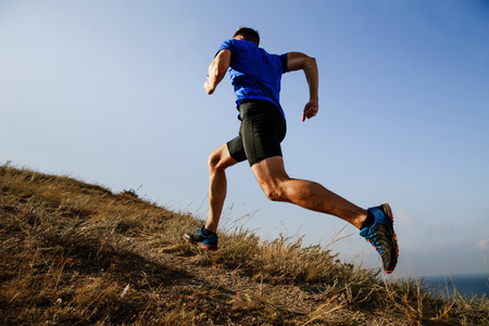 dynamic running uphill on trail male athlete runner side view