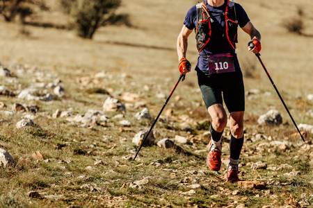 man athlete runner running mountain trail with trekking poles Stock Photo