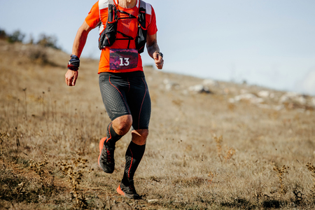 young male athlete runner running mountain trail