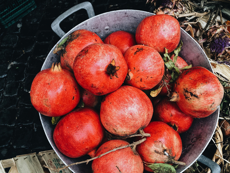 harvest ripe pomegranate in a zinc bucket Stock Photo