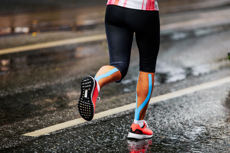 blue kinesio tape on calf muscle women runner