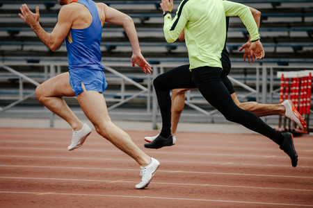 group men sprinters runners running in athletic track
