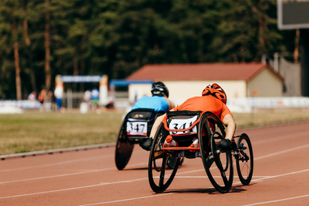 two athletes racer on wheelchair racing track stadium