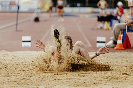 Weitsprung Frauen Athlet Jumper Landung im Sand mit Spray Standard-Bild