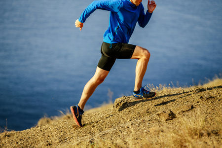 man runner dynamic running on steep slope of mountain