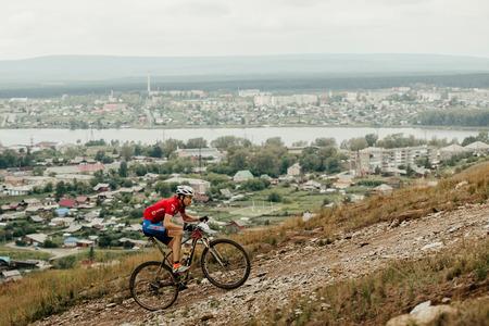 V.Ufaley, Russia - August 12, 2018: cyclist mountain biker riding steep climb during race XCM Big stone