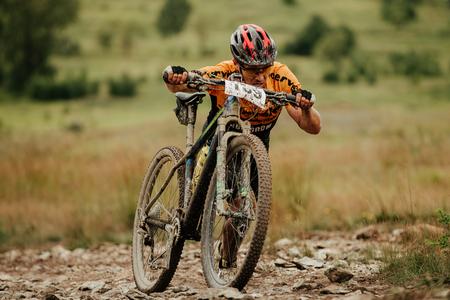 V.Ufaley, Russia - August 12, 2018: dirty cyclist mountain biker climb in steep walk during race XCM Big stone Editoriali