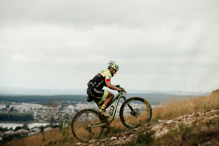 V.Ufaley, Russia - August 12, 2018: athlete cyclist mountain biker riding uphill during race XCM Big stone