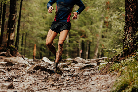 dirty runner athlete running down trail stones in woods
