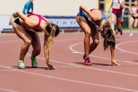 two women runners starting position of relay race 4 on 100 meters Stockfoto