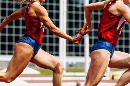 estafetteloop doorgeven van baton dames teamlopers Stockfoto