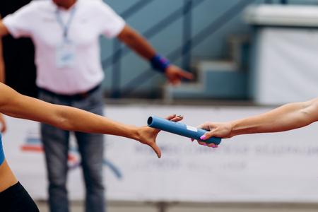 passing of baton from hand to hand women relay race Foto de archivo