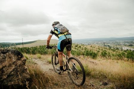 ciclista uomo con zaino in mountain bike a cavallo sulle cime delle montagne